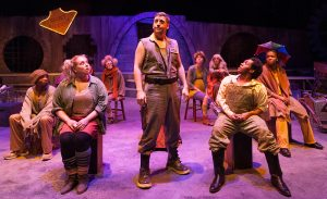 """The downtrodden masses of """"Urinetown"""" with leader Bobby B. Strong (Keith Claverie) in center. (Photo by John Barrois)"""