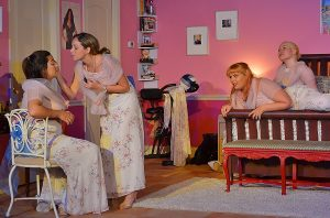Trisha (Amanda-Lynn Williams) consoles Frances (Icela Marliese). At right, Mindy (Rei Capote) and Georgeanne (Thiana Berrick) look on with interest. (Tripp (Kevin Rubi) gets himself into what he feels is the best position to snap the perfect photograph of the reluctant bridesmaids. (Photo by Dennis Lyzniak)