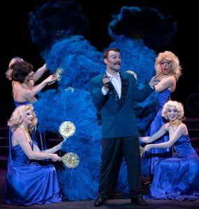 Nightclub girls surround Georges (Jamie Michael Parnell) with feather-like material. (Photo by George Wentzler)