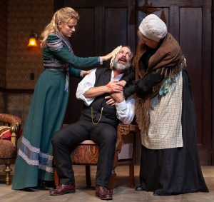 Emmy (Sarah Durn), left, comforts her father, Torvald (Trey Burvant) as Anne Marie (Liann Pattison) grabs hold of him. (Photo by John Barrois)