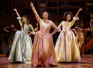 Ta'Rea Campbell, center, as Angelica Schuyler snaps with Danielle Sostre as Peggy Schuyler, right. Shoba Narayan, left, has been replaced by Erin Clemons as Eliza Hamilton. (Photo by Joan Marcus)