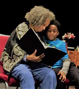Lena Younger (Carol Sutton) reads to her grandson Travis (Ellington Benoit). (Photo by Tommye Myrick)