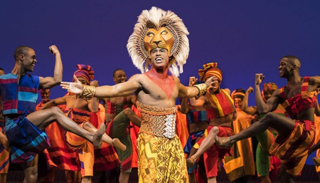 Jared Dixon as Simba with the cast of