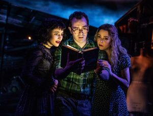 Lydia (Sarah Anne Caruso) reads the Books of the Recently Departed with Adam (Rob McClure) and Barbara (Kerry Butler) Maitland. (Photo by Matthew Murphy)