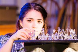 "Laura Wingfield (Julia DeLois) with her ""glass menagerie."" (Photo by James Kelley)"
