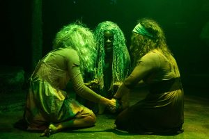 """Rachel Finley, center,one of the """"weird sisters"""" plots with her fellow """"witches. (Photo by Ryan Artnst)"""
