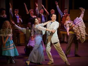 """Professor"" Harold Hill (John Tartaglia) and Marian Paroo (julie Kleiner) dance, along with ensemble members of The Wick Theatre's production of The Music Man. (Photo by Amy Pasquantonio)"