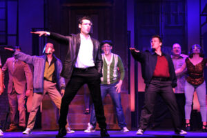 Sage Spiker as Calogero with Doo Wop singers behind him. (Photo courtesy Broadway Palm Dinner Theater)